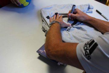 Thierry Omeyer signe un autographe sur un maillot de handball