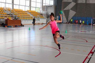 Stagiaire fille qui effectue un saut en extension pendant un entraînement de handball
