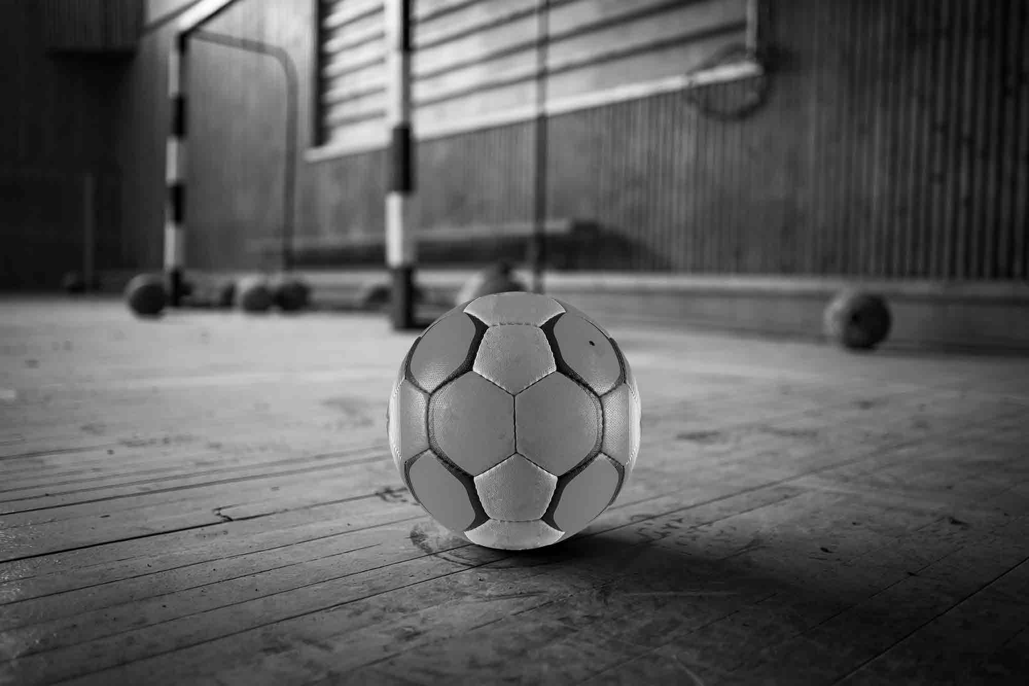 Un ballon de handball en premier plan posé sur un terrain de hand vide